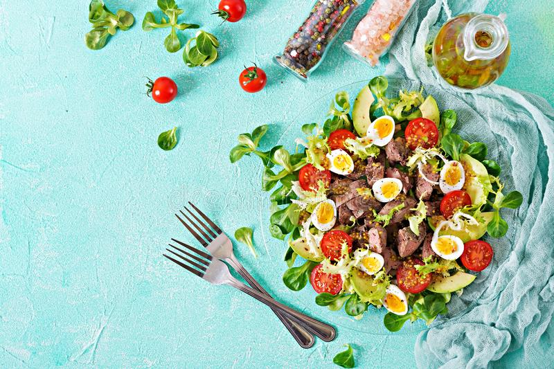 Warm salad from chicken liver, avocado, tomato and quail eggs. Healthy dinner. Dietary menu. stock photography