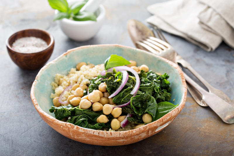 Warm salad with kale, chickpeas and quinoa. Warm quinoa salad with kale, chickpeas and red onion royalty free stock photo