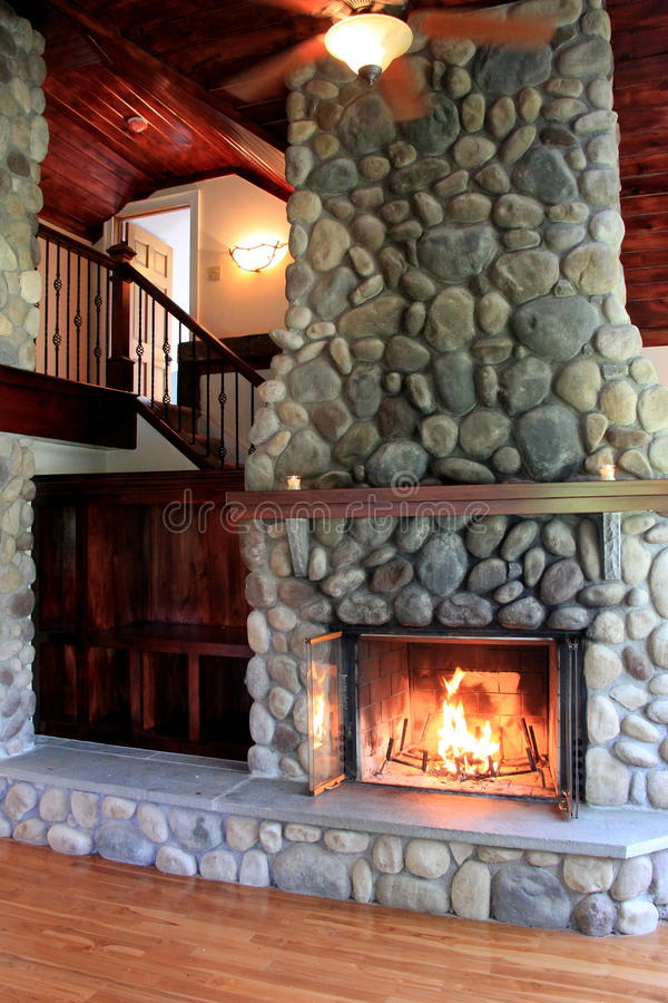 Warm scene in lit stone fireplace showcasing craftsmanship in rustic home. Gorgeous image showcasing detail of craftsmanship in warmly lit stone fireplace in stock photography