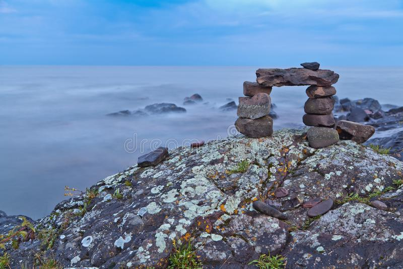 Rock cairn on the lakeshore. Warm summer evening at Lake Superior. Trail cairn on mossy royalty free stock photos