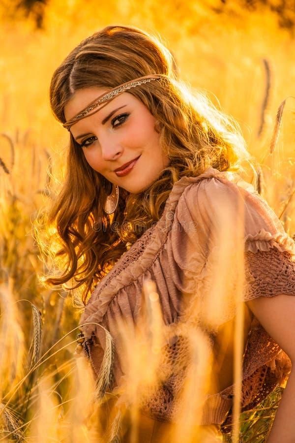 Warm summer haze seventies hippie girl in grainfield. stock image