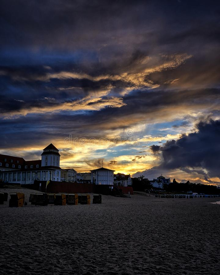 Warm summer night on sandy beach by sea. Sunset at Baltic sea in Binz. Rays of sun shine through the low rare cirrus clouds. Rügen, island, city stock photos