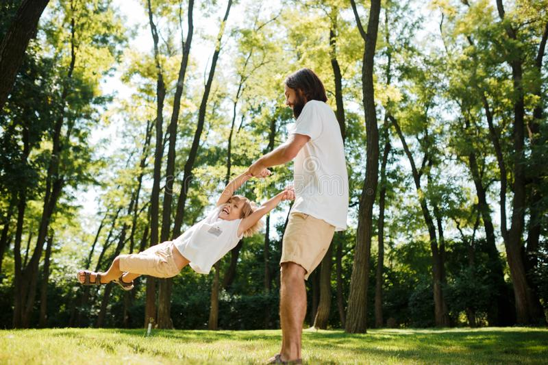 Warm sunny day. Cheerful little boy with his father in white t-shirts are playing outdoor. Father is circling son around.  stock photos