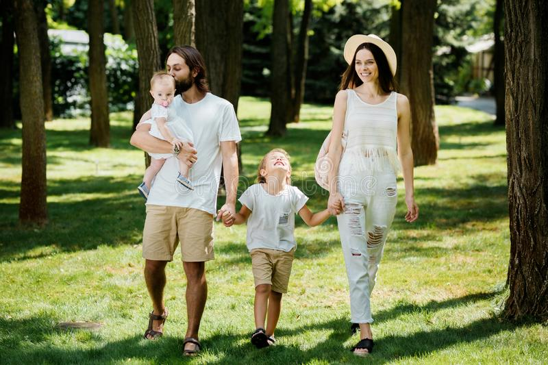 Warm sunny day. Handsome father, beautiful mother and two kids dressed in the white casual clothes happily walks in the. Park royalty free stock images