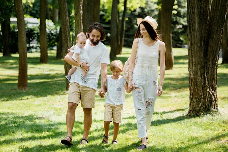 Warm sunny day. Handsome father, beautiful mother and two kids dressed in the white casual clothes happily walks in the. Park stock images