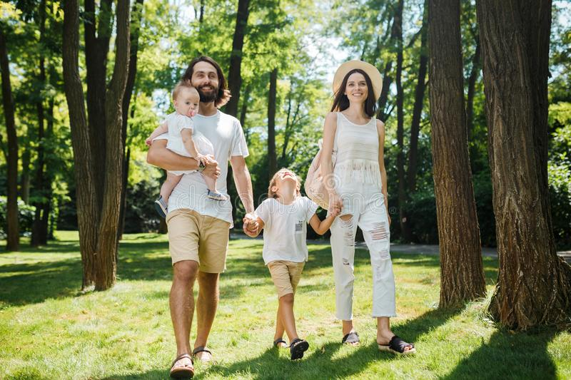 Warm sunny day. Handsome father, beautiful mother and two kids dressed in the white casual clothes happily walks in the royalty free stock photos