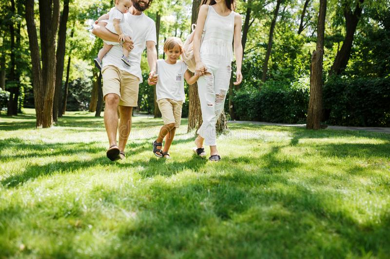 Warm sunny day. Handsome father, beautiful mother and two kids dressed in the white casual clothes happily walks in the stock images