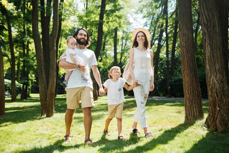 Warm sunny day. Handsome father, beautiful mother and two kids dressed in the white casual clothes happily walks in the royalty free stock photography