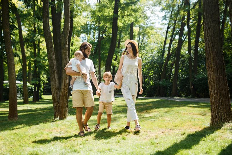 Warm sunny day. Handsome father, beautiful mother and two kids dressed in the white casual clothes happily walks in the stock image