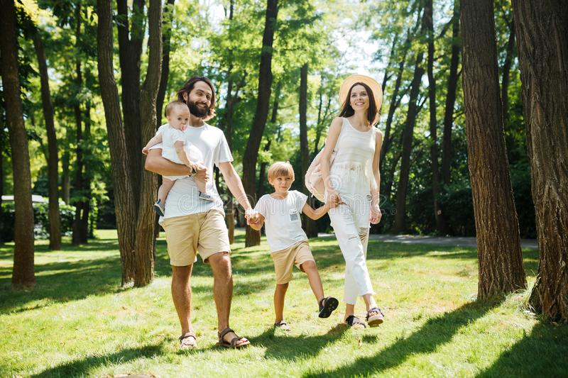 Warm sunny day. Handsome father, beautiful mother and two kids dressed in the white casual clothes happily walks in the stock photos