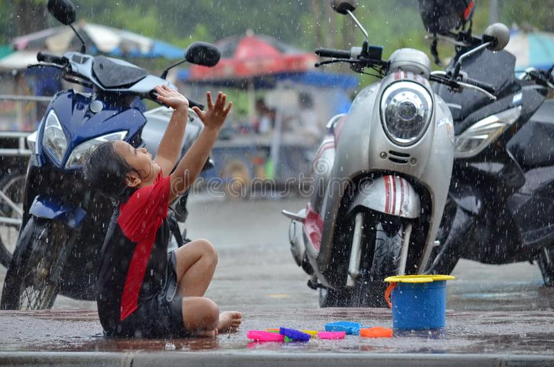 Young Asian girl appears to be giving thanks as she plays in the rain during monsoon season in Thailand. stock photo