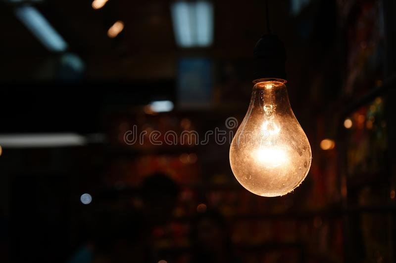 Warm tone old style hanging light bulb decoration. Copy space stock photo