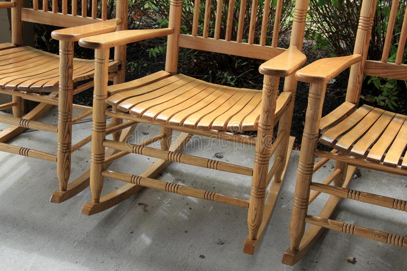 Warm-toned wood of three Adirondack rocking chairs royalty free stock photography