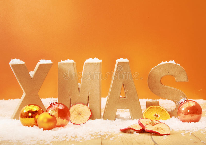 Warm toned Xmas background. With wooden letters for Xmas in snow with orange and gold decorations and dried apple and orange slices against an orange background stock photography