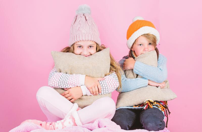 Warm up your winter wear with cute and cozy accessories. Siblings wear winter warm hats sit on pink background. Children. Boy and girl warm up with pillows and royalty free stock photos