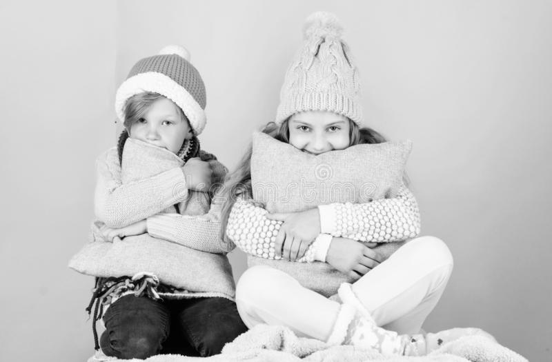 Warm up your winter wear with cute and cozy accessories. Siblings wear winter warm hats sit on pink background. Children. Boy and girl warm up with pillows and royalty free stock images