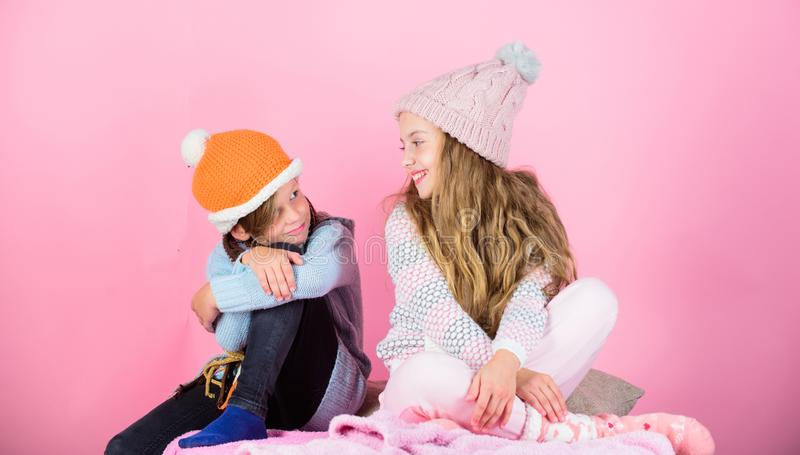 Warm up your winter wear with cute and cozy accessories. Siblings wear winter warm hats sit on pink background. Children. Boy and girl warm up with sweaters and stock photos