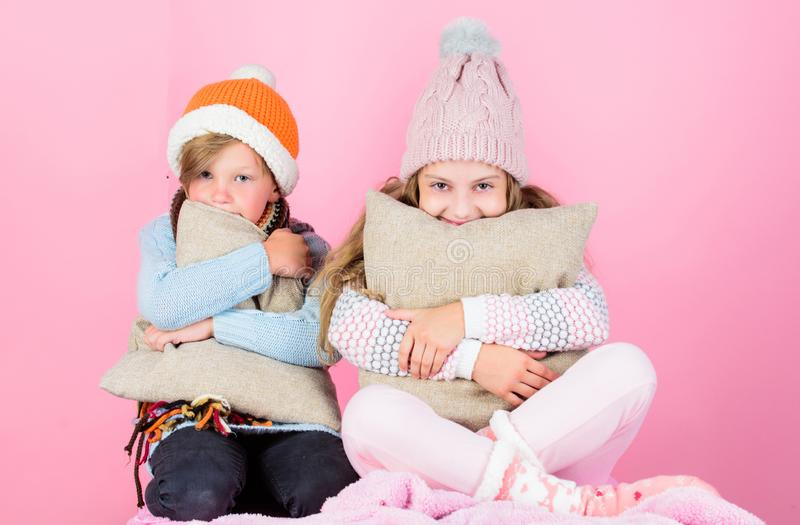 Warm up your winter wear with cute and cozy accessories. Siblings wear winter warm hats sit on pink background. Children. Boy and girl warm up with pillows and royalty free stock photography