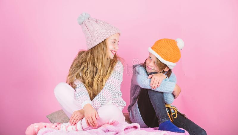 Warm up your winter wear with cute and cozy accessories. Siblings wear winter warm hats sit on pink background. Children. Boy and girl warm up with sweaters and royalty free stock images