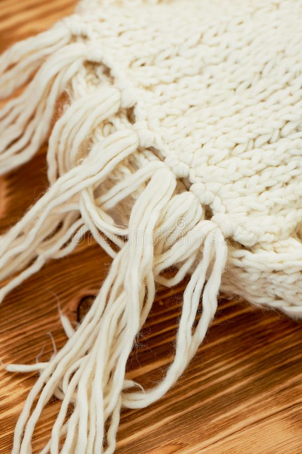 Warm white scarf chunky knit keep on the wood surface.Macro. The atmosphere is warm and autumn. Warm white scarf chunky knit keep on the wood surface. Macro. The royalty free stock photo