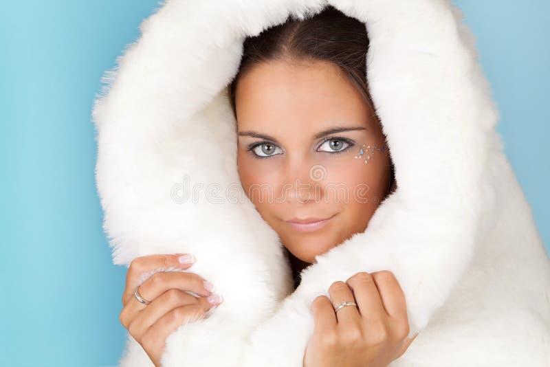 Warm winter coat. Winter girl with white fur hat wearing warm fur coat royalty free stock image