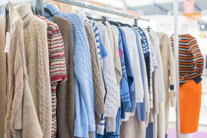 warm winter demi raglans on white shopping racks with silver metal parts on clothes shop. bright different clothes on the rack bef stock photography