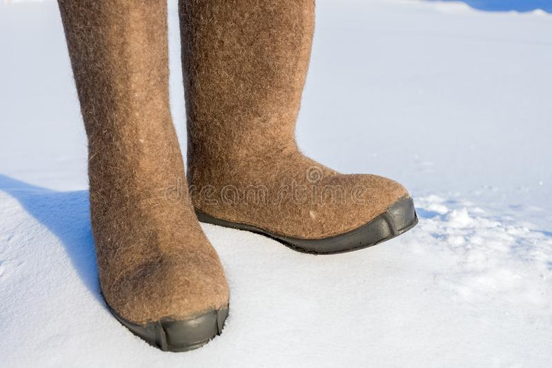 Warm winter shoes made of felt close up in the snow. Photo outdoors on a frosty day stock photography