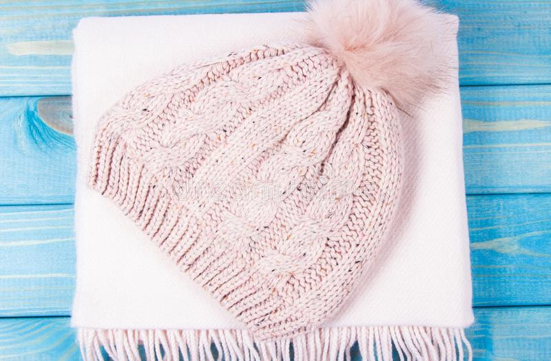 Warm winter knitted clothes - hat, scarf, on a blue background. stock photos
