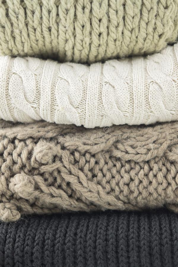 Warm woolen knitted winter and autumn clothes, folded in a pile. Sweaters, scarves. Close-up. royalty free stock photos