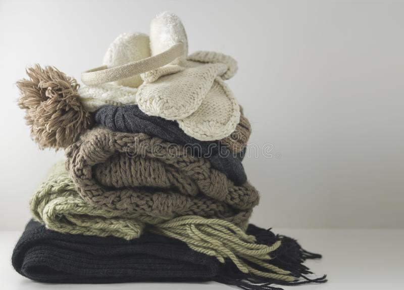 Warm woolen knitted winter and autumn clothes, folded in a pile on a white table. Sweaters, scarves, gloves, hat. Headphones. Place for text. Copyspace stock photography