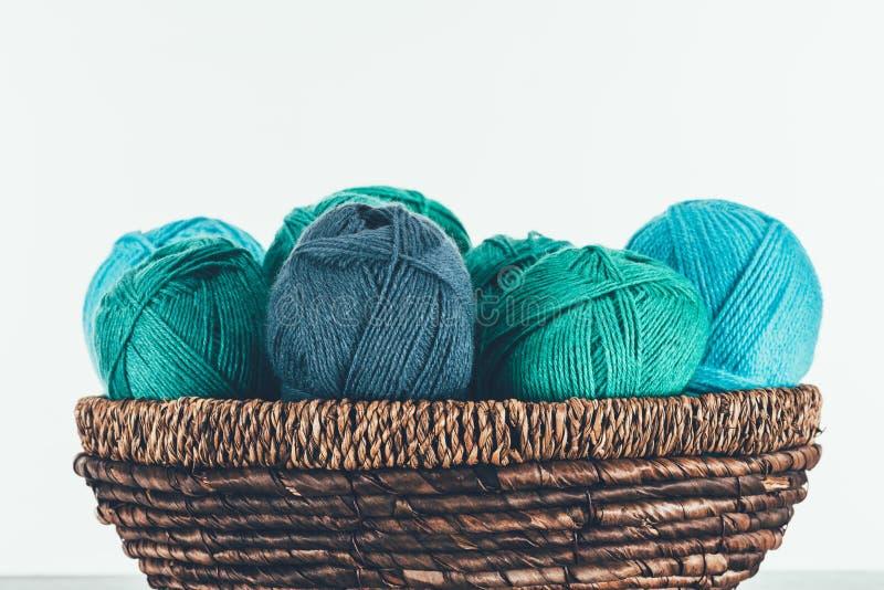 Warm yarn balls in wicker basket. Blue and green warm yarn balls in wicker basket on white royalty free stock photos
