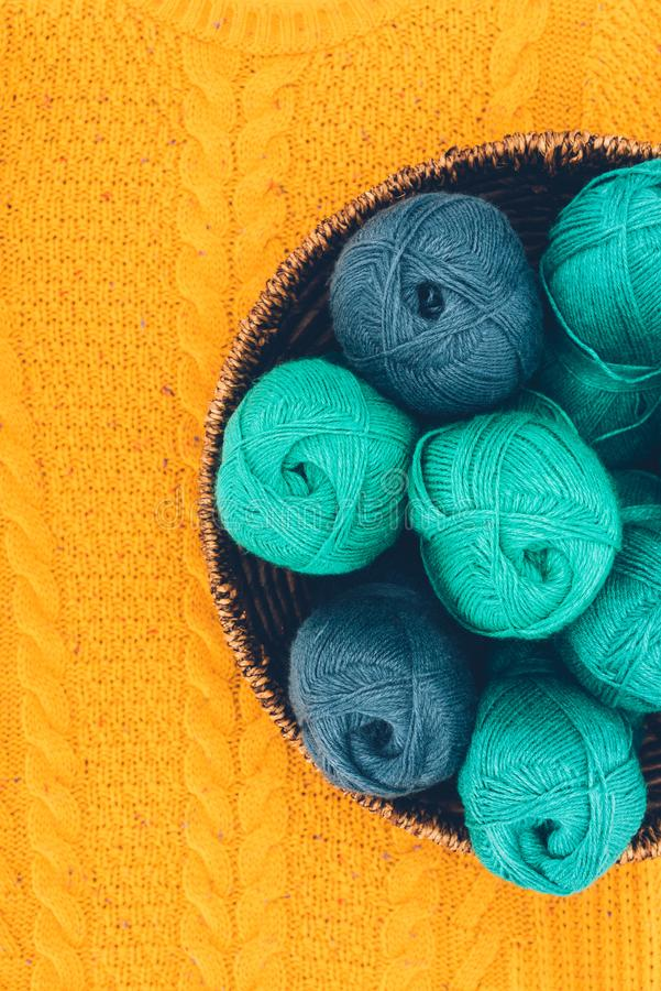 Warm yarn balls in wicker basket. Top view of blue and green knitting yarn balls in wicker basket on yellow knit royalty free stock photos