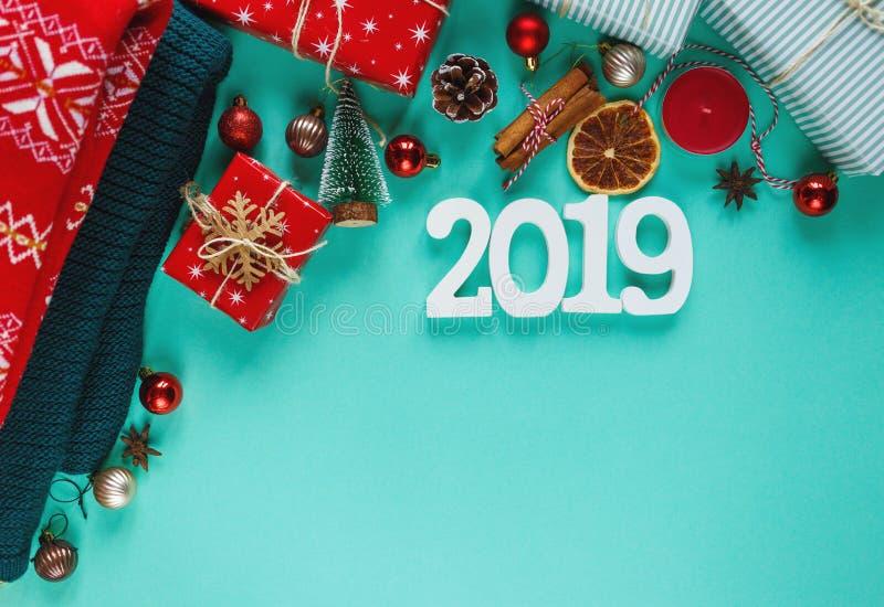 Warme, gemütliche Winterkleidung, weiße Nr. 2019 und Weihnachtsdekorationsrahmen auf grünem Hintergrund lizenzfreies stockfoto