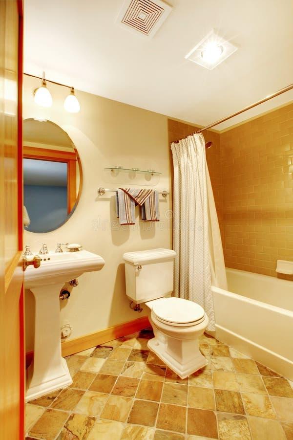 Warme gouden badkamers met natuurlijke tegels royalty-vrije stock afbeeldingen