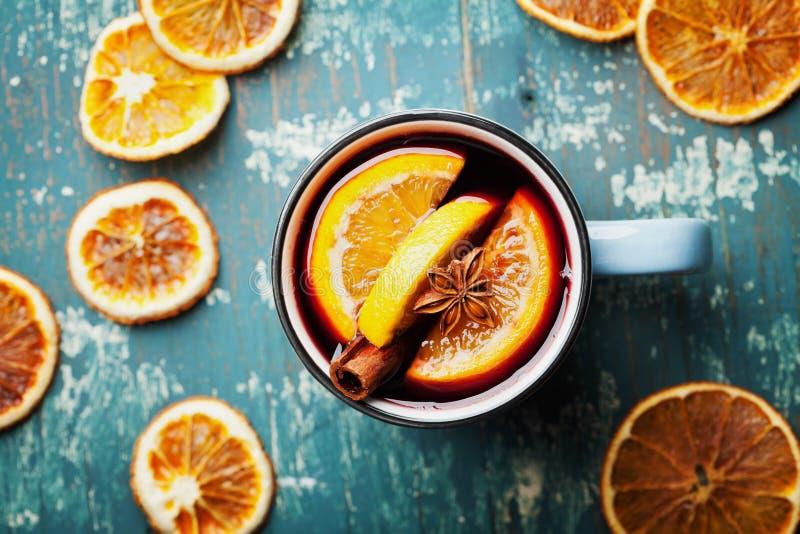 Warme Kerstmis overwoog wijn of gluhwein met kruiden en oranje plakken op houten de bovenkantmening van de wintertalingslijst Tra royalty-vrije stock foto
