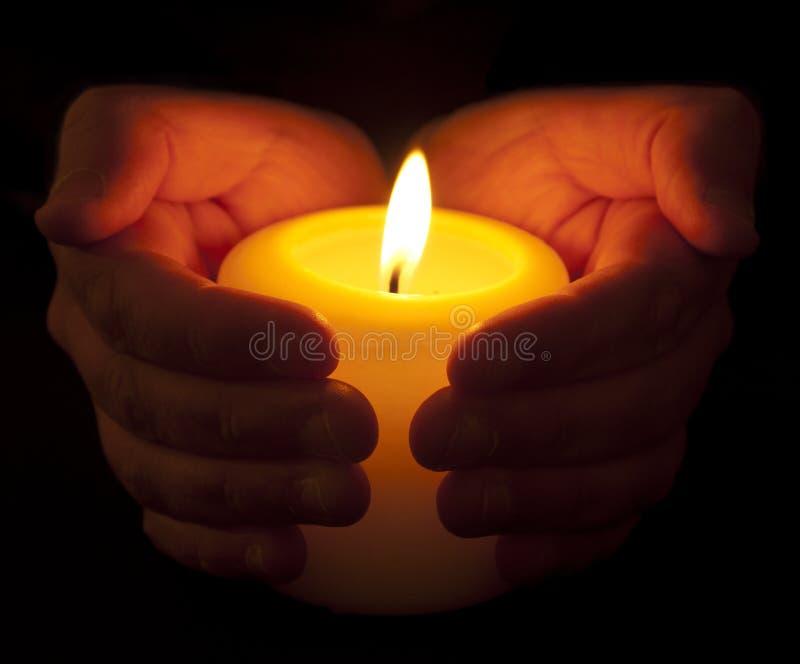 Warme Kerze in schalenförmigen Händen lizenzfreie stockbilder