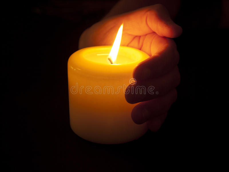 Warme Kerze in schalenförmiger Hand stockbild