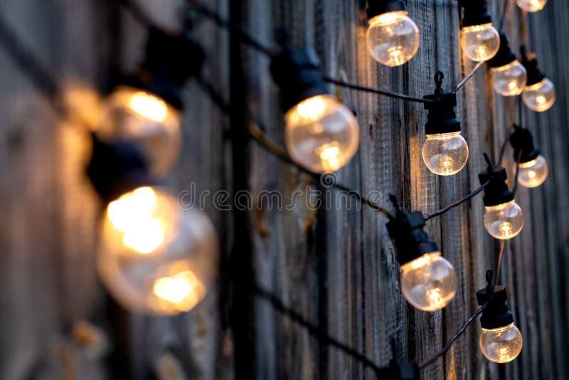 Warme kleuren LEIDENE gloeilampen op oude houten achtergrond in de tuin, copyspace, het openluchtconcept van verlichtingsdecirati royalty-vrije stock foto's