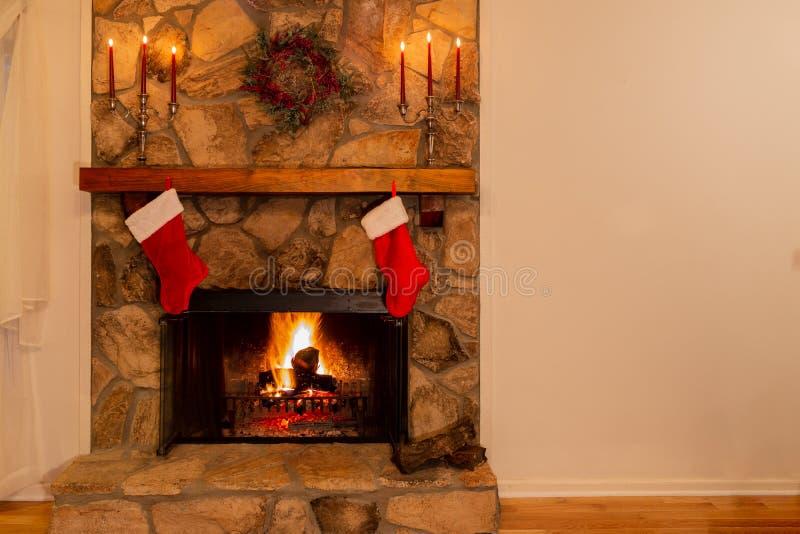 Warme open haard met kroon, candelabras en twee Kerstmiskousen in het familiehuis stock foto's
