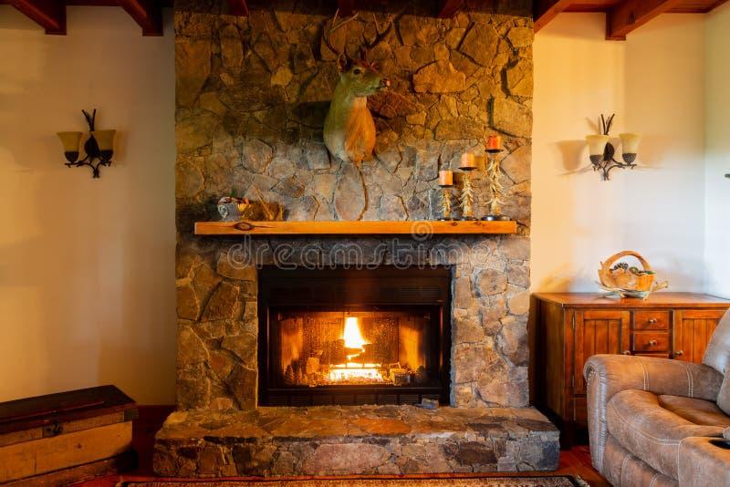 Warme open haard in woonkamer met een hertenhoofd opgezet op steenopen haard stock afbeeldingen