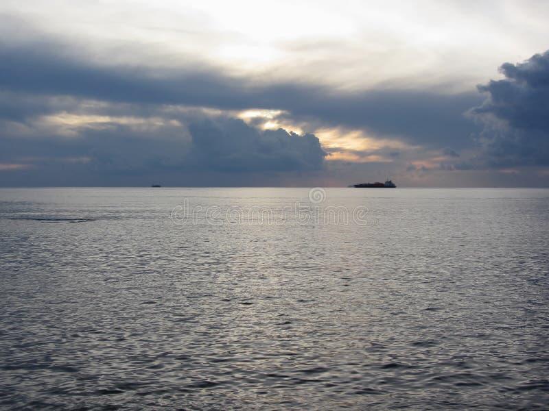 Warme overzeese zonsondergang met vrachtschip bij de horizon Reuzencumulonimbus de wolken zijn in de hemel Toscanië, Italië stock afbeelding