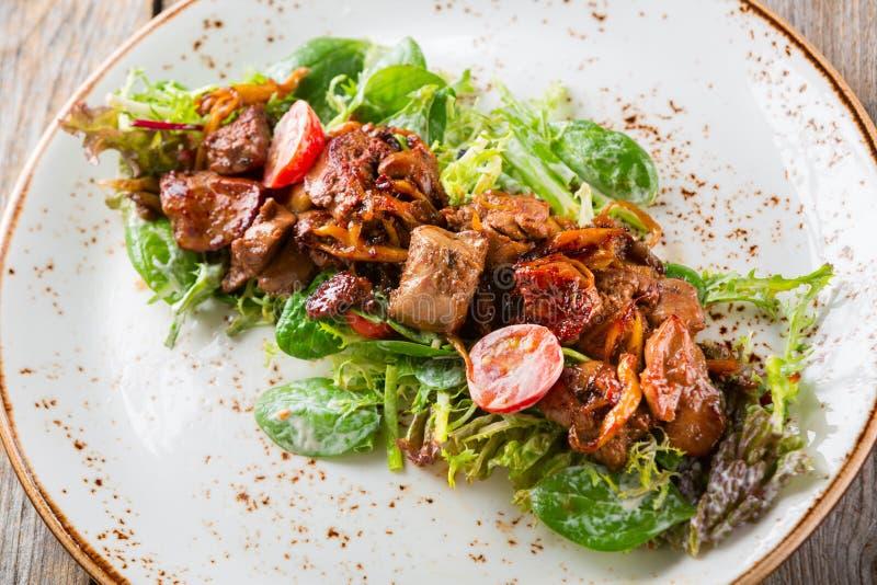 Warme salade met geroosterde kippenlever, tomaten en paddestoelen royalty-vrije stock fotografie