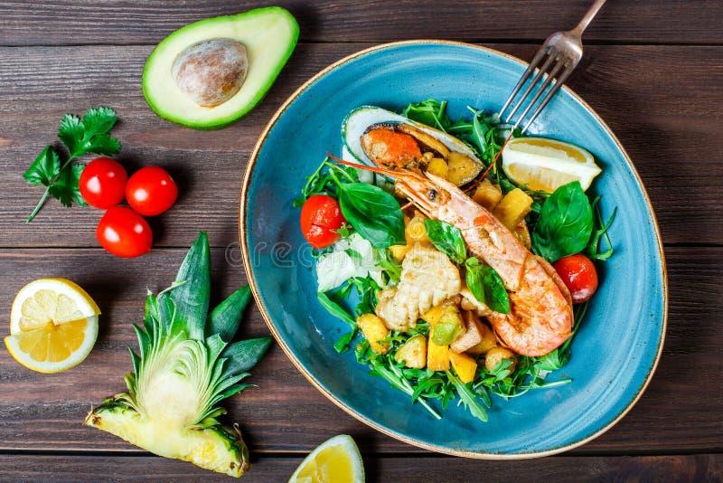 Warme salade met zeevruchten, langoustine, mosselen, garnalen, pijlinktvis, kammosselen, mango, ananas, avocado, arugula op houte royalty-vrije stock afbeelding