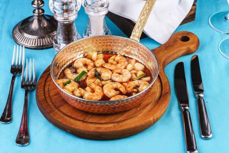 Warme salade van geroosterde vissenstukken, garnalen en mosselen in een pan, met geroosterde groenten royalty-vrije stock foto