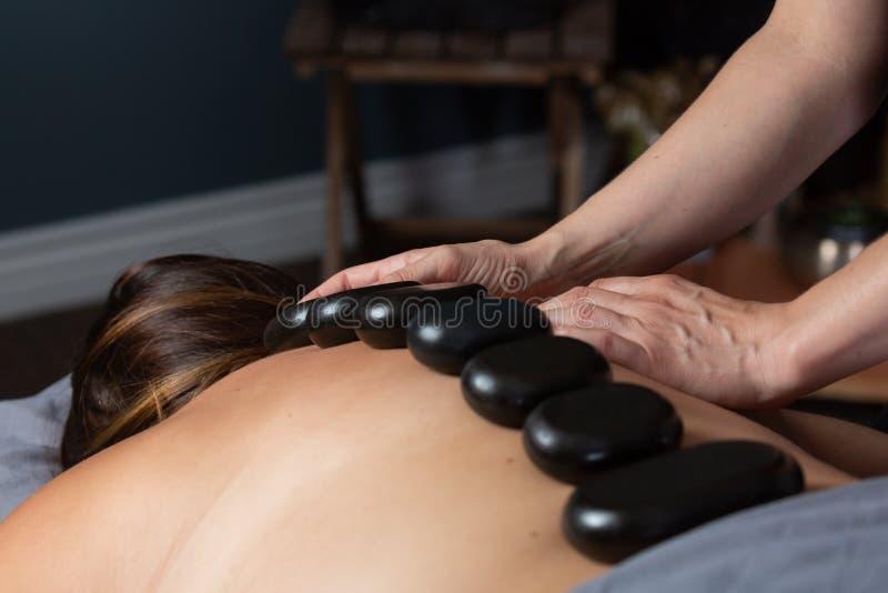 Warme stenen en de handen van de therapeut op de rug van een massagecliënt stock fotografie
