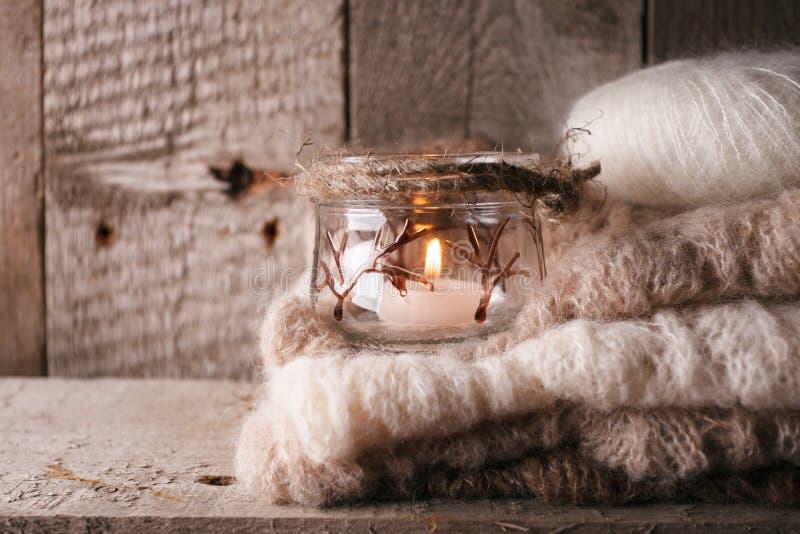 Warme Strickjacke auf hölzerner rustikaler Bank, Kerze, gemütliche alltägliche Szene der Ruhe Fallherbstwochenende Einfarbiges Ko stockbild