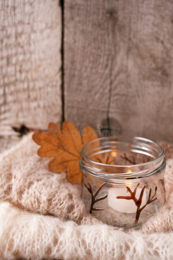 Warme sweater op houten rustieke bank, Kaars, Stille comfortabele eenvoudige scène Het weekend van de dalingsherfst Zwart-wit con stock afbeeldingen