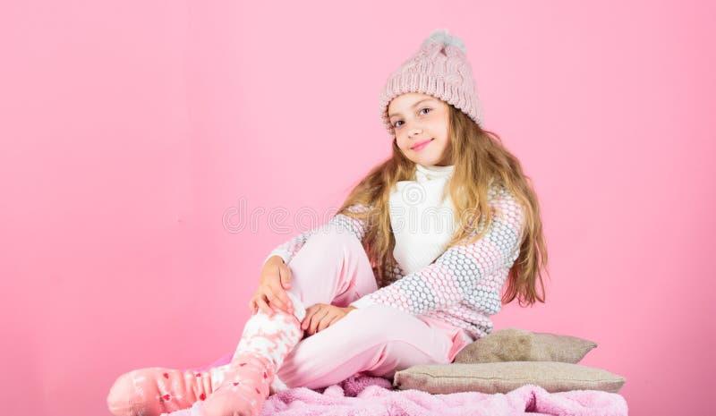 Warme Zusätze, die Sie gemütlich dieser Winter halten Gestrickter warmer Hut des Kindermädchens Abnutzung, der rosa Hintergrund s stockfotografie