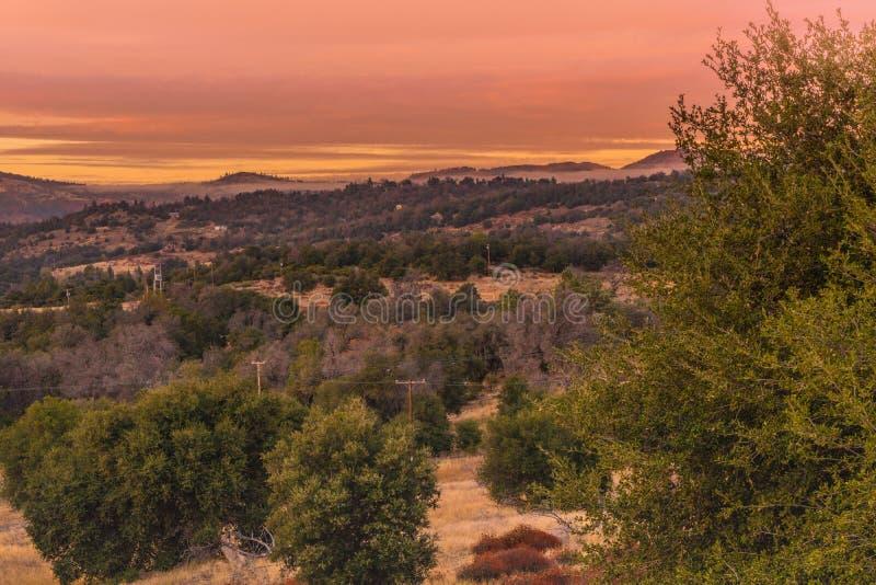 Warmer Farb-Sonnenunterganghimmel, Orange, Rot, Lavendel tont, in Süd-Kalifornien-Hügeln im Herbst, Eichen in den Vordergrundberg stockbilder