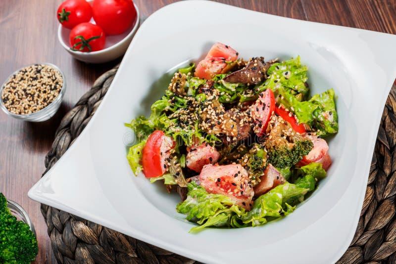 Warmer Salat mit der hühnerleber, Tomaten, Kopfsalat verlässt, Brokkoli auf Holztisch Gesunde Nahrung lizenzfreie stockfotografie